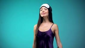 Femme asiatique heureuse dans les pyjamas et le sentiment les yeux bandés bons après sommeil de nuit image stock
