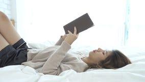 Femme asiatique heureuse de mode de vie jeune appréciant le mensonge sur le plaisir de livre de lecture de lit dans les vêtements clips vidéos