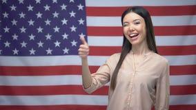 Femme asiatique heureuse montrant des pouces- et clignant de l'oeil sur le fond de drapeau des Etats-Unis banque de vidéos
