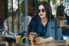 Femme asiatique heureuse tenant son téléphone dans un café Photographie stock