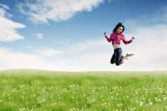 Femme asiatique insouciante faisant un grand saut sur le pré photo libre de droits