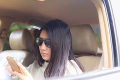 Femme asiatique jouant le smartphone dans la voiture noire photographie stock