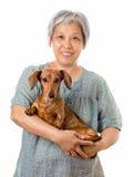 Femme asiatique mûre avec le chien de teckel Photo stock