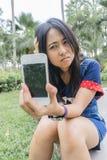Femme asiatique malheureusement au téléphone intelligent cassé Photographie stock libre de droits