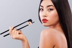 Femme asiatique mangeant des sushi et des petits pains sur un fond gris Copiez l'espace image libre de droits