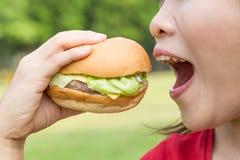 Femme asiatique mangeant l'hamburger Photo libre de droits