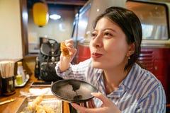 Femme asiatique mangeant la brochette japonaise dans l'izakaya photographie stock libre de droits