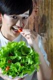 Femme asiatique mangeant la tomate fraîche Image libre de droits