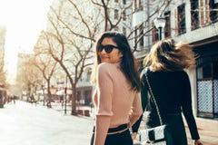 Femme asiatique marchant avec son ami sur la rue Photographie stock libre de droits