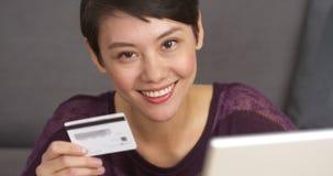 Femme asiatique mignonne heureuse tenant la carte de crédit images stock
