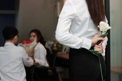 Femme asiatique navrée déprimée tenant une rose blanche derrière elle de retour avec un fond d'amant de couples dans le jour de v Photos libres de droits