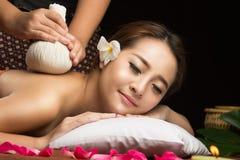 Femme asiatique obtenant le massage de fines herbes thaïlandais de compresse Images stock
