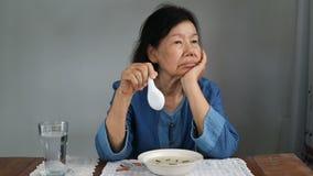 Femme asiatique pluse âgé ennuyée avec la nourriture banque de vidéos