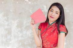 Femme asiatique portant la robe traditionnelle rouge tenant la poche rouge avec l'espace pour le texte images stock