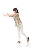 Femme asiatique poussant ou se penchant sur le mur Image libre de droits