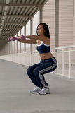 Femme asiatique s'accroupissant avec des haltères photos stock