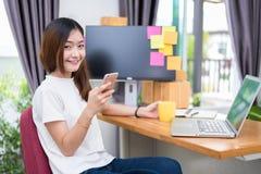 Femme asiatique s'amuser tandis qu'utilisant l'Internet sur l'ordinateur portable et le pH image libre de droits