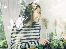 Femme asiatique s'asseyant au café et riant avec l'ami et l'étiquette d'utilisation Images stock