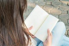 Femme asiatique s'asseyant en parc public pour lire un livre blanc Images libres de droits