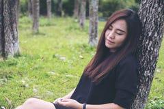 Femme asiatique s'asseyant et dormant par l'arbre avec le fond vert de forêt photographie stock