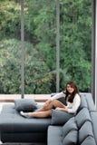 Femme asiatique s'asseyant sur le sofa près de grands vitraux, seul détendant dans la maison avec la forêt verte à l'arrière-plan images libres de droits