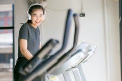 Femme asiatique s'exerçant au gymnase sur un entraîneur croisé Photographie stock