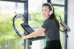 Femme asiatique s'exerçant au gymnase sur un entraîneur croisé Photos stock