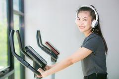 Femme asiatique s'exerçant au gymnase sur un entraîneur croisé Photos libres de droits