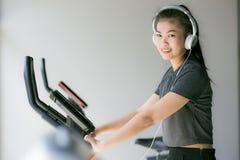 Femme asiatique s'exerçant au gymnase sur un entraîneur croisé Images libres de droits