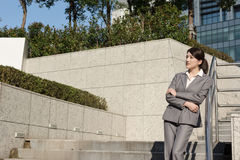 Femme asiatique sûre d'affaires se tenant dans en dehors de du bureau dedans Image stock
