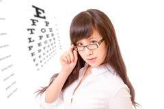 Femme asiatique scrutant au-dessus du dessus des lunettes à côté de l'eyechart Photographie stock