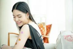 Femme asiatique se sentant heureusement dans l'amour et s'asseyant sur le sofa avec des autocollants de coeur sur ses bras Images libres de droits