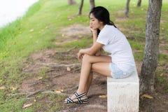 Femme asiatique seule en parc Photo stock