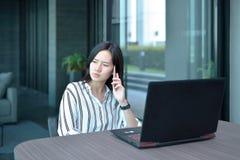 Femme asiatique soumise à une contrainte d'affaires occasionnelles téléphonant et pensant dedans pour Photos libres de droits