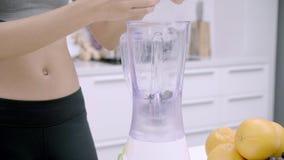 Femme asiatique sportive à l'aide du mélangeur pour faire le jus de raisins dans la cuisine, belle femelle dans l'habillement de  clips vidéos