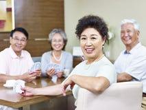 Femme asiatique supérieure dans le jeu de carte Photo stock