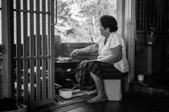 Femme asiatique supérieure faisant cuire dans la cuisine Image stock