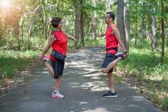 Femme asiatique supérieure heureuse avec l'homme ou les muscles personnels de cuisse de bout droit d'entraîneur au parc photos stock