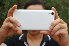 Femme asiatique tenant et employant l'arrière futé d'exposition de téléphone photo stock