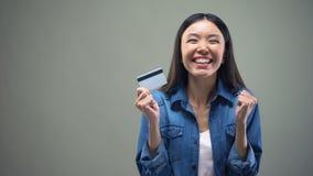 Femme asiatique tenant la carte de crédit dans des mains, services d'argent liquide de retour, fond gris banque de vidéos