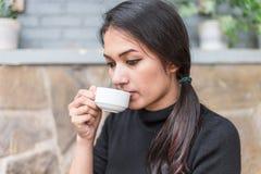 Femme asiatique tenant la tasse blanche et buvant d'un café ou d'un thé chaud en café Images libres de droits