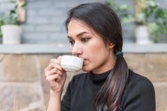 Femme asiatique tenant la tasse blanche et buvant d'un café ou d'un thé chaud en café Images stock