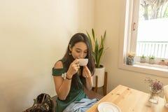 Femme asiatique tenant la tasse blanche et buvant d'un café ou d'un thé chaud en café Photos libres de droits