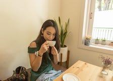 Femme asiatique tenant la tasse blanche et buvant d'un café ou d'un thé chaud en café Photos stock