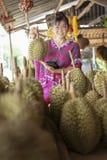 Femme asiatique tenant le fruit de durian et le sourire toothy avec le happine image stock