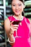 Femme asiatique tenant le verre de vin Photos stock