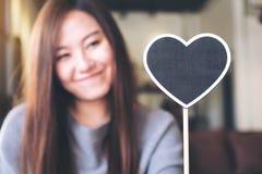 Femme asiatique tenant un signe vide de tableau noir de forme de coeur avec se sentir heureux et dans l'amour Images libres de droits