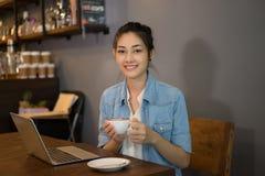 Femme asiatique travaillant avec l'ordinateur portable et le café potable en café photo libre de droits