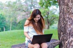 Femme asiatique travaillant sur un ordinateur portable souriant à un jardin ou à un parc Image stock