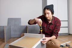 Femme assemblant un tiroir de coffre pour de nouveaux meubles de chambre à coucher photographie stock